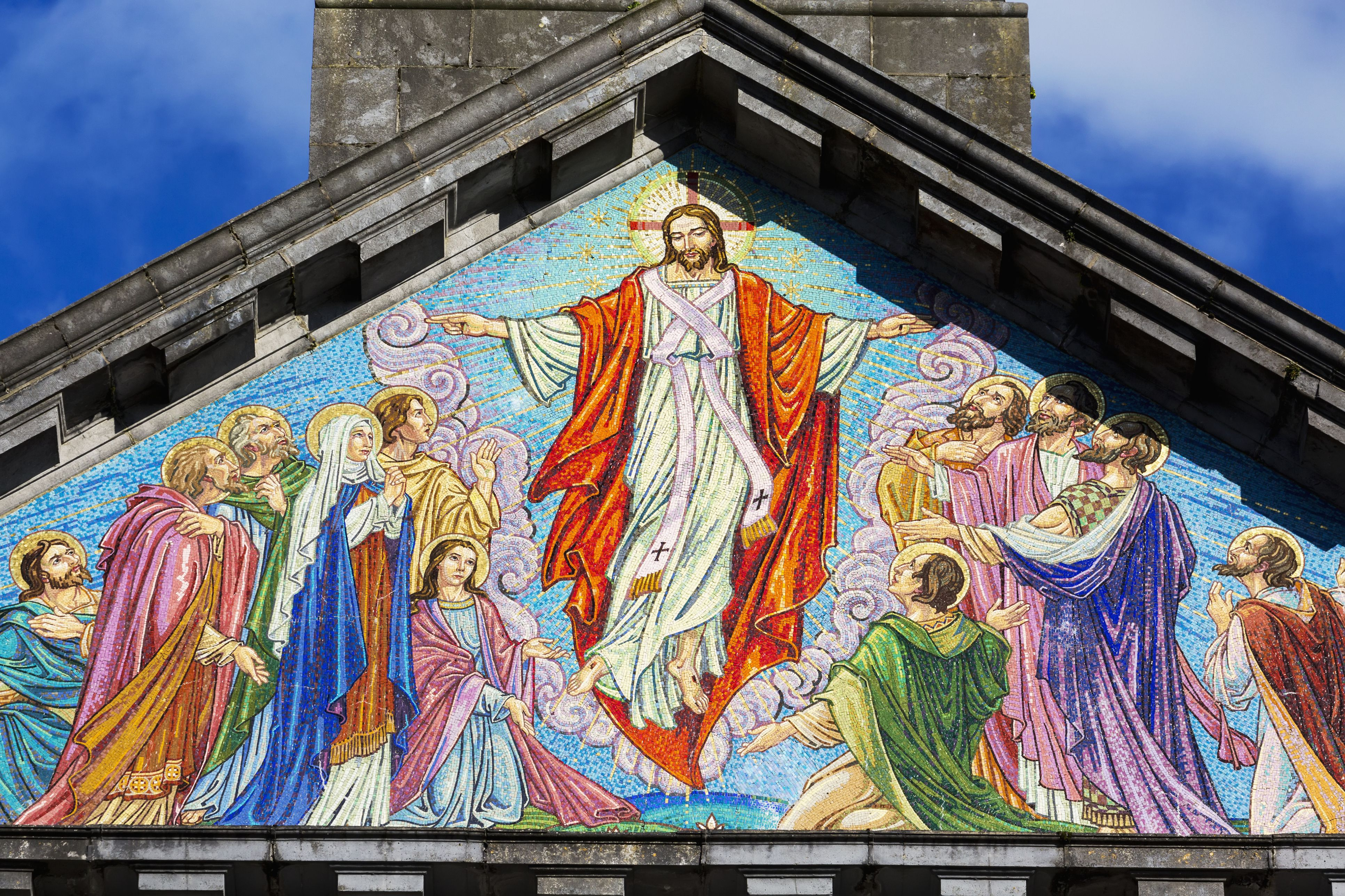 Close up of colourful mosaic of the ascension of Christ on church face with stone peak and blue sky; Cashel, County Tipperary, Ireland