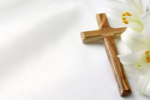 Easter lilies and cross on a white satin background