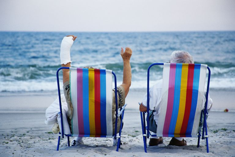 Mature men in beach chairs, one with hand in cast, rear view