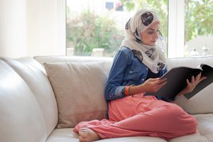 Arab woman reading a magazine on the sofa.