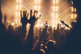 Silhouettes of concert-goers with hands raised against stage lights