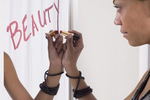A teenage girl writing beauty on a mirror in lipstick