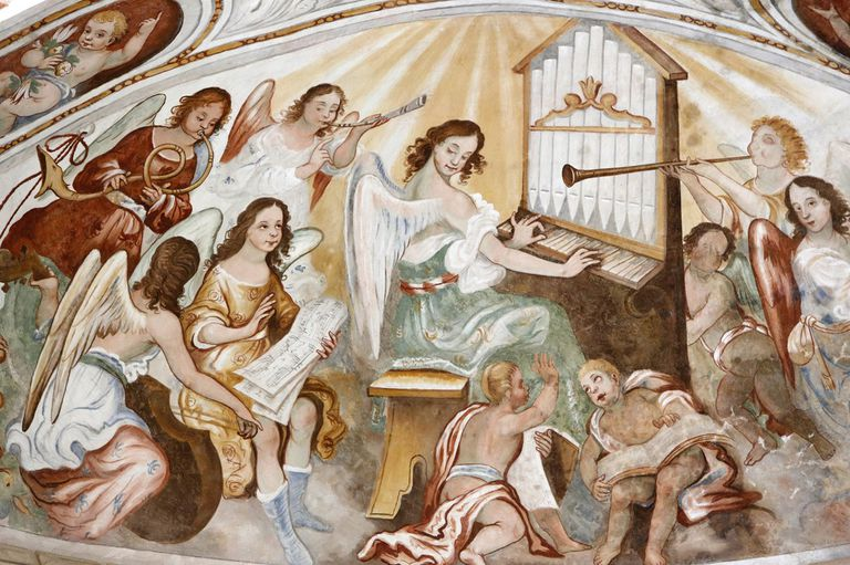 Painting of angels playing instruments and singing together.