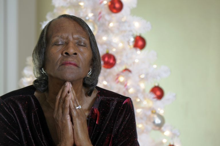 Senior African American Woman Praying with Christmas Tree in Background
