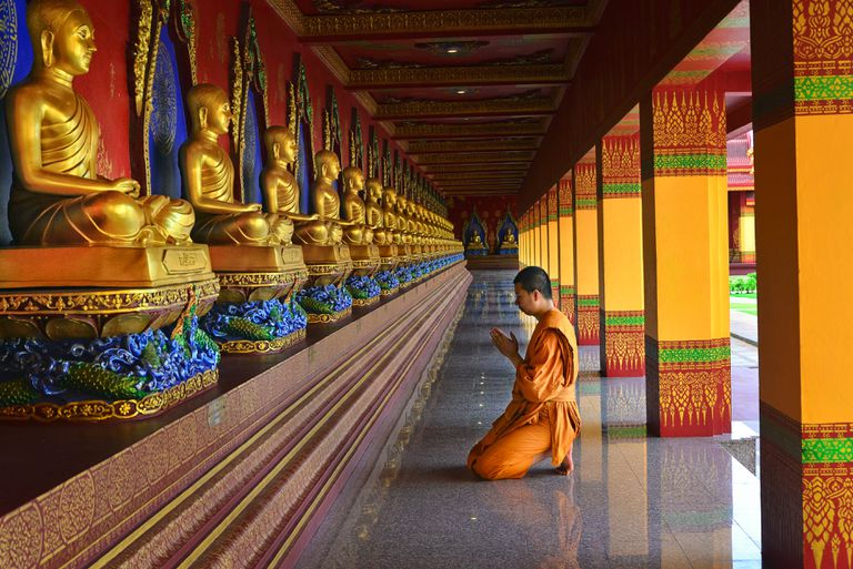 Buddhist Monk praying at a temple in Krabi, Thailand.