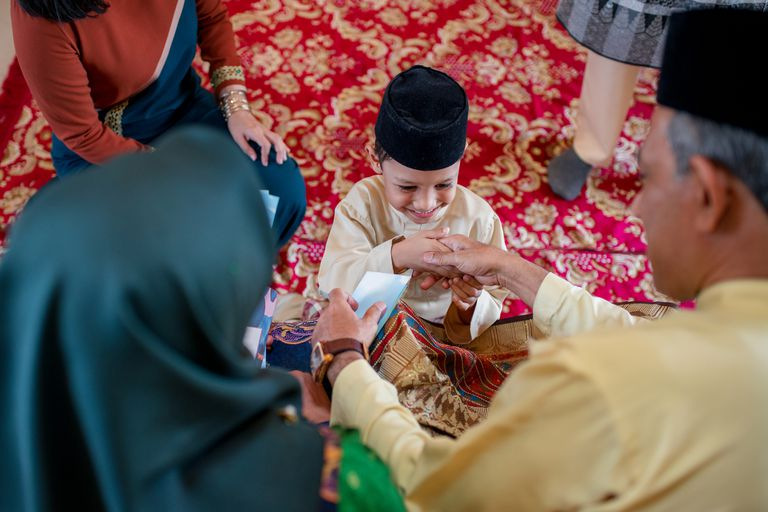 A young boy receives a gift from his grandparents on Eid al-Fitr