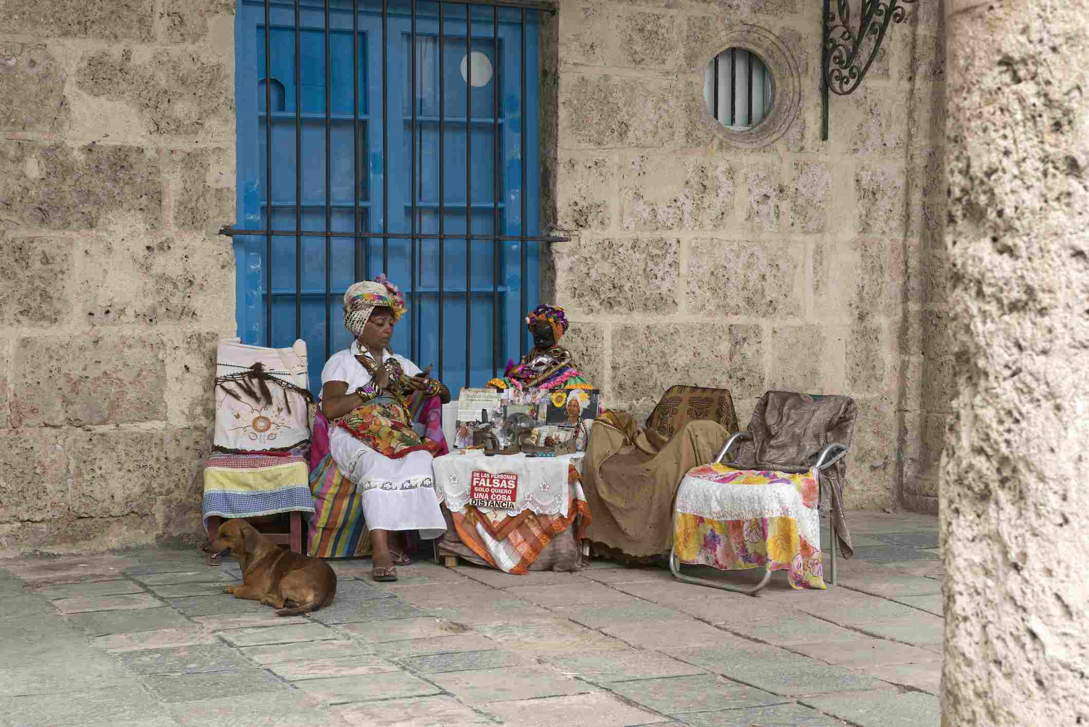 A fortune teller or Cuban Priestess in traditional dress using her smart phone.