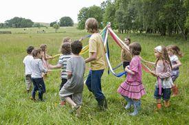 Kids dancing round maypole in meadow