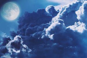 Blue full moon rising at night between the clouds.