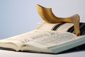 Religious Judaic objects used for prayer - a shofar, tallis, and prayer book.