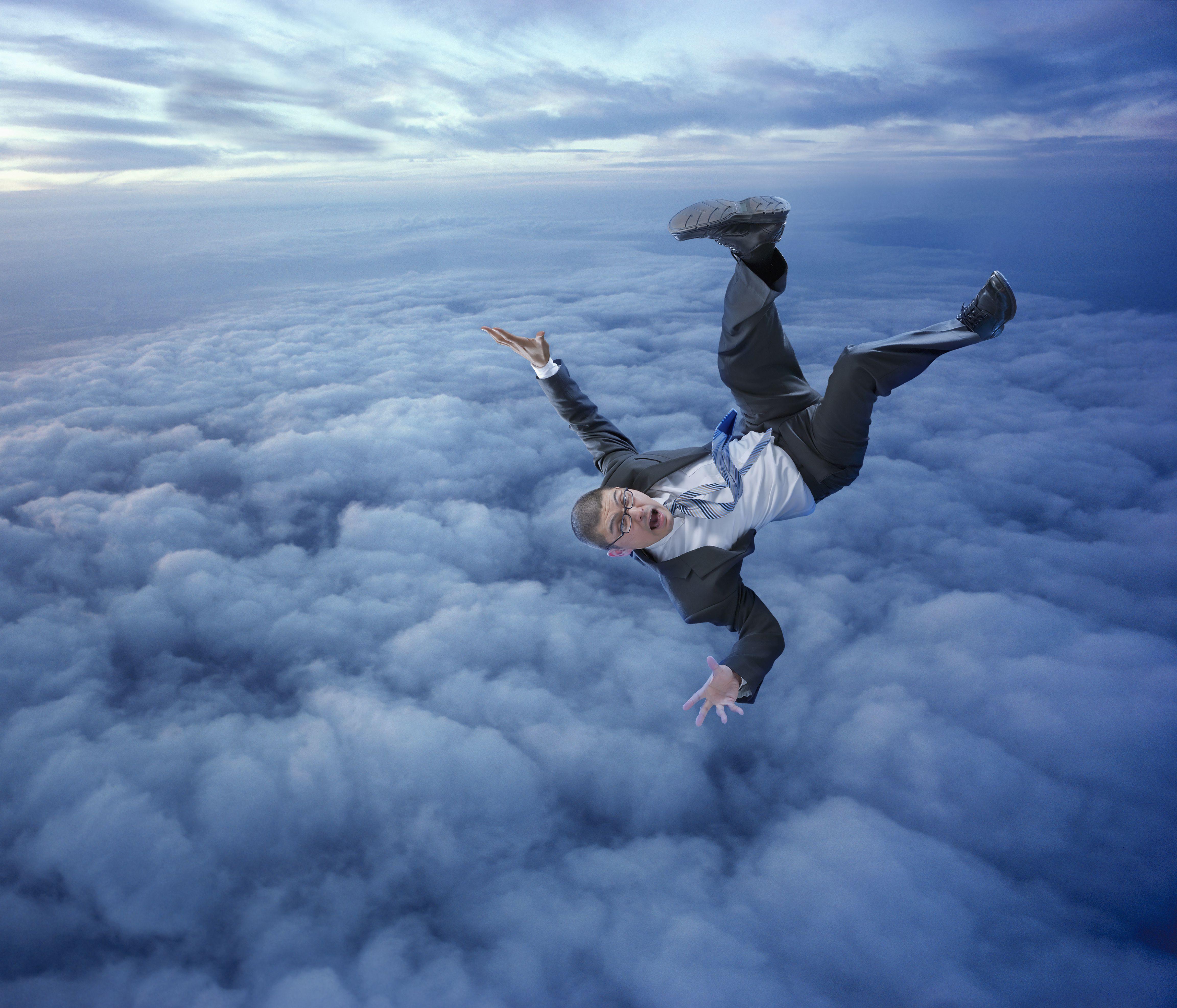 Businessman falling in clouds