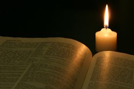Open bible lit by candlelight