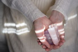 Hands of Caucasian woman holding crystals
