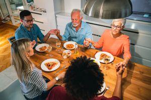 Family prays before eating dinner