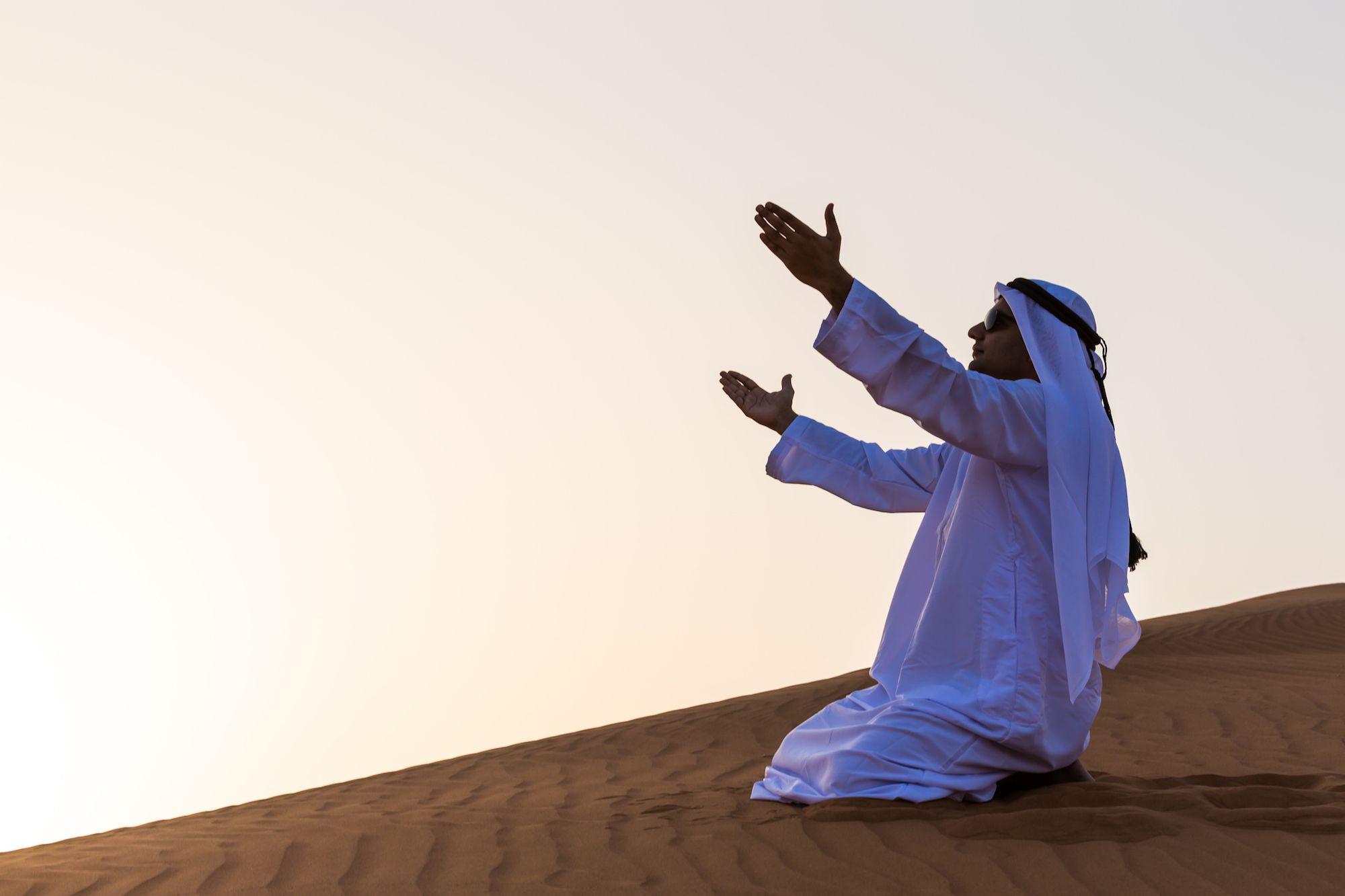 man praying in the desert
