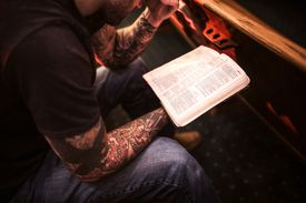 Man with tattoos reading the Bible