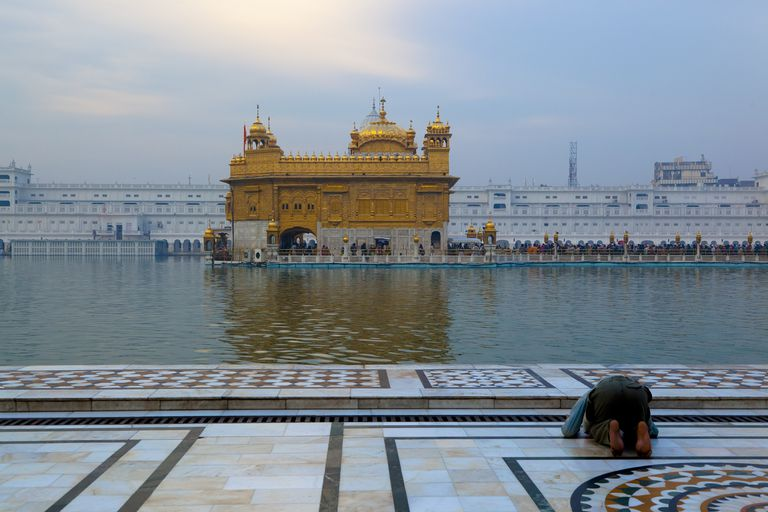 Man praying before a golden temple and a large reflecting pool.