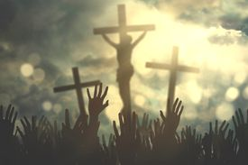 Close-Up Of Silhouette Hands Against Jesus Christ