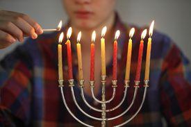 Teenager lighting Hannuka candles