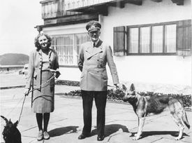 Adolf Hitler and Eva Braun with two dogs in front of a house.