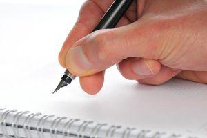 A hand holding a fountain pen