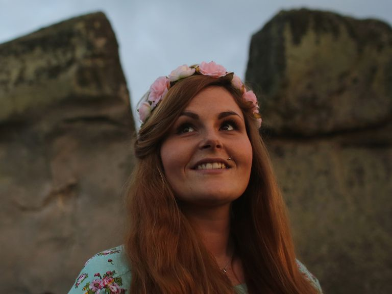 A woman with flowers in her hair in a ruins