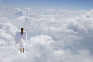 Woman With Angel's Wings Standing on Clouds