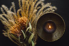 Brass Bowl with Black Candle and Dried Feather Grass and Flowers on Black Table