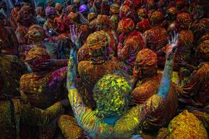 People covered in colorful powders celebrating Holi