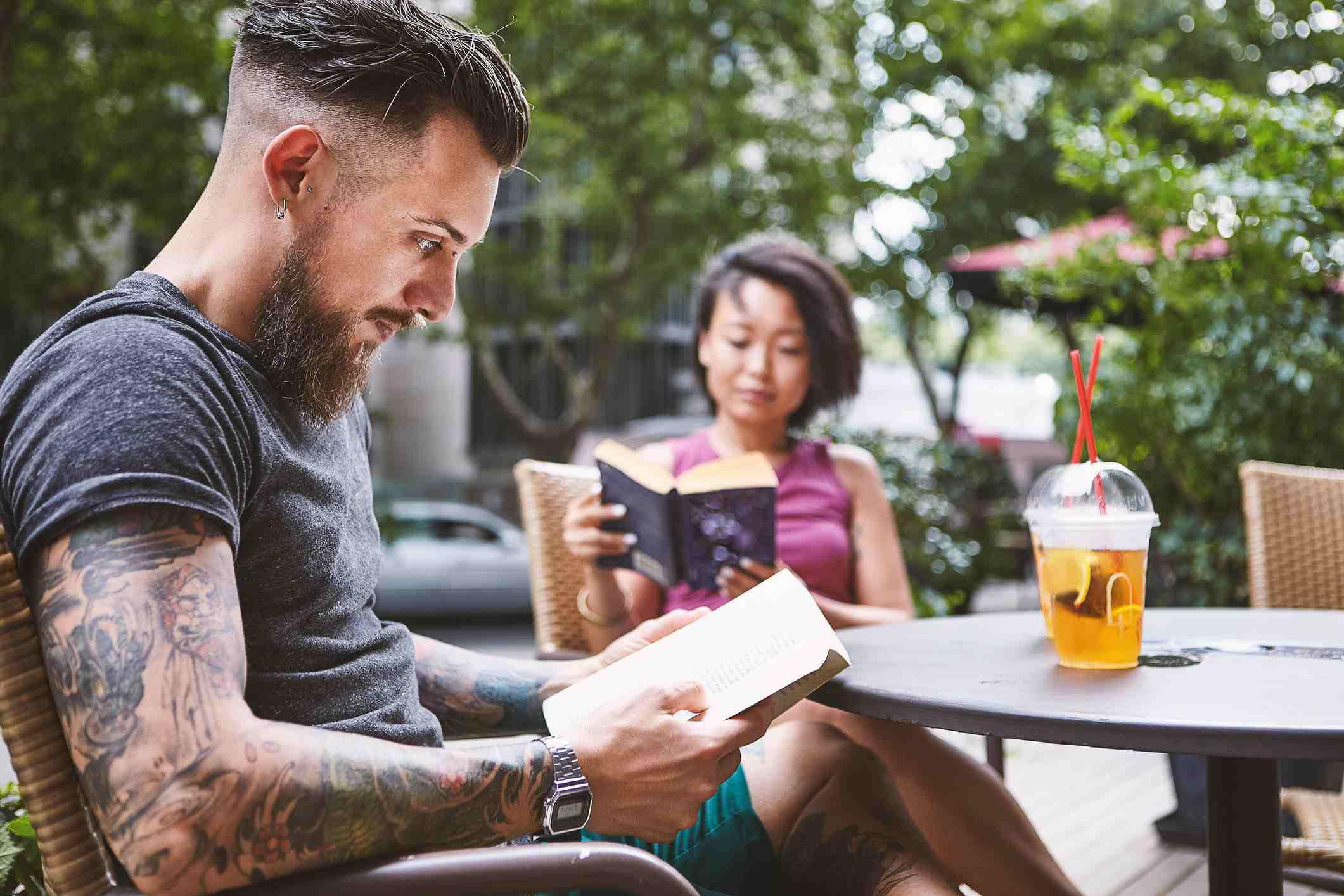 Couple reading books at sidewalk cafe