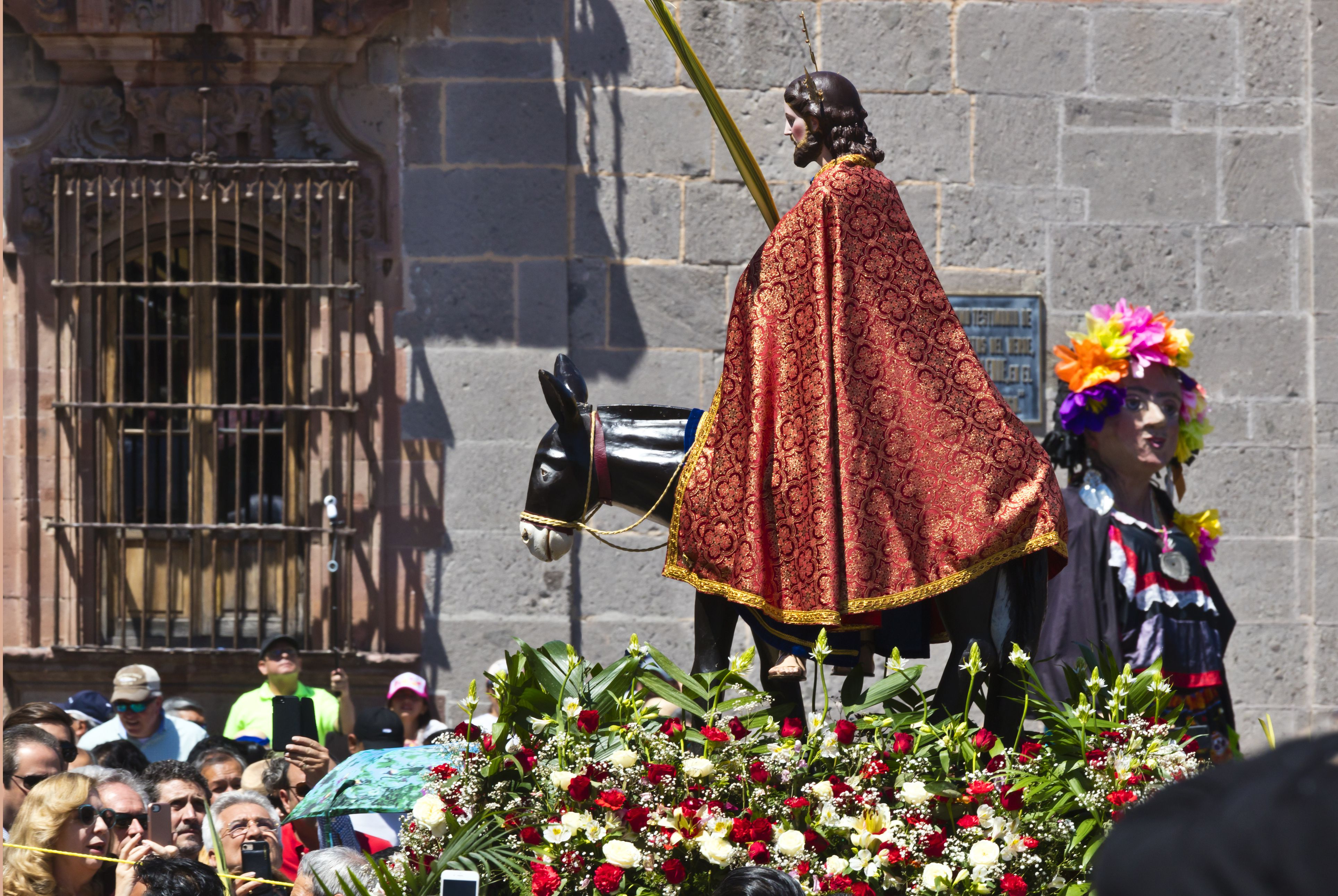 A statue of JESUS CHRIST is carried in the PALM SUNDAY PROCESSION from Parque Juarez to the Jardin - SAN MIGUEL DE ALLENDE, MEXICO