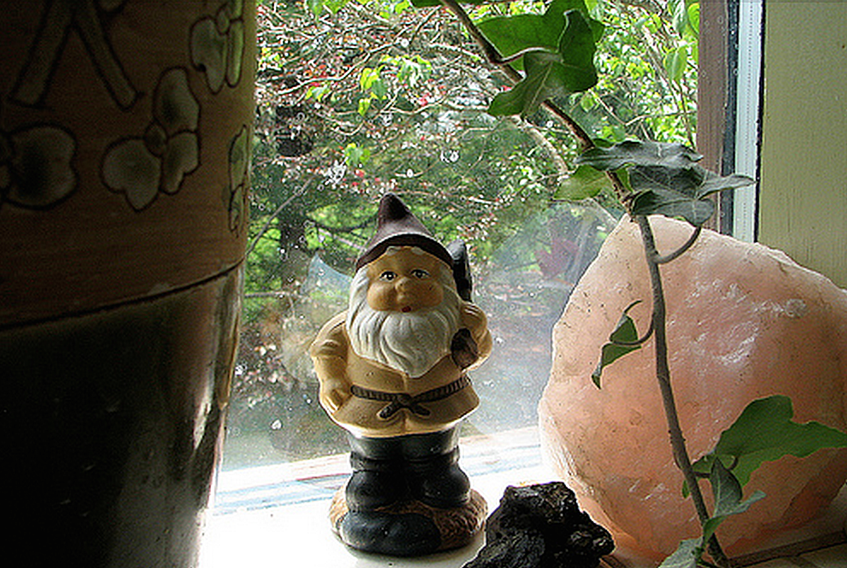 Gnome figurine on a windowsill next to a pink crystal