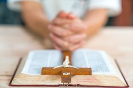 Christian woman praying with hands crossed and Holy Bible by his side on wooden desk in church, top view