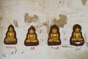 Four carved golden statues of Buddha in wall