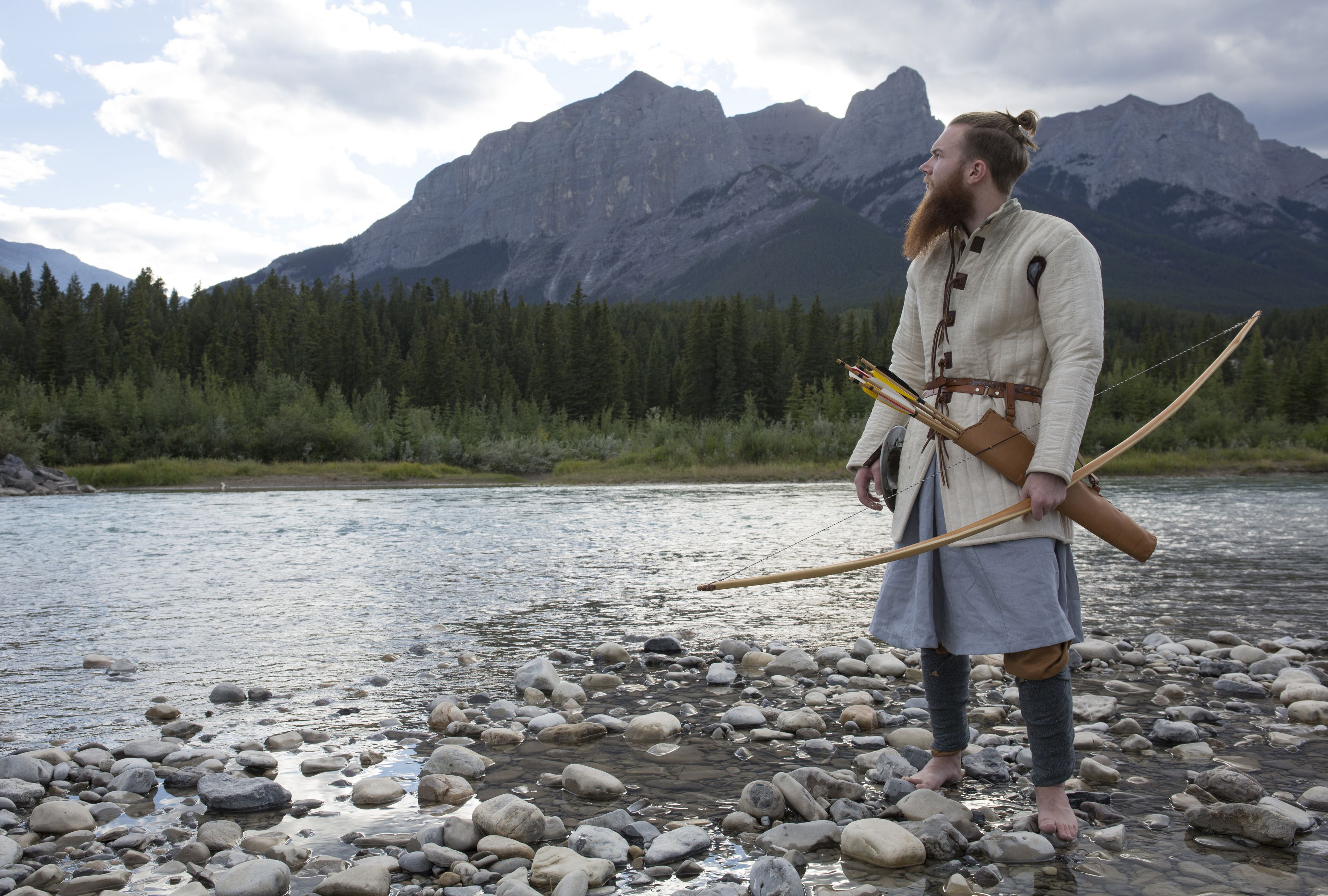 Man in viking warrior dress hunts by mtn river