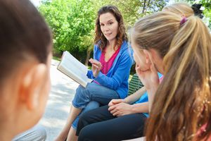 Woman reading bible with youth group outdoors