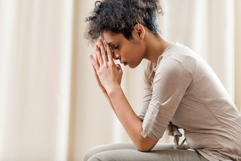 African American woman praying at home