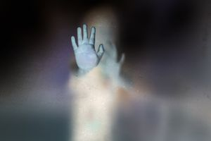Soft shutter of ghost hands behind the frosted glass with negative film style