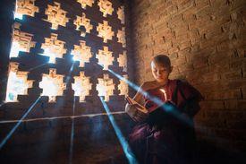 Burmese novice reading the Buddhist book inside ancient temple in Bagan plain, Myanmar.