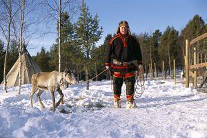 A reindeer breeder and a reindeer.