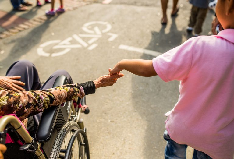 Woman in wheel chair and child holding hands