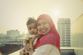 Mother in a hijab smiling with her baby on a city rooftop