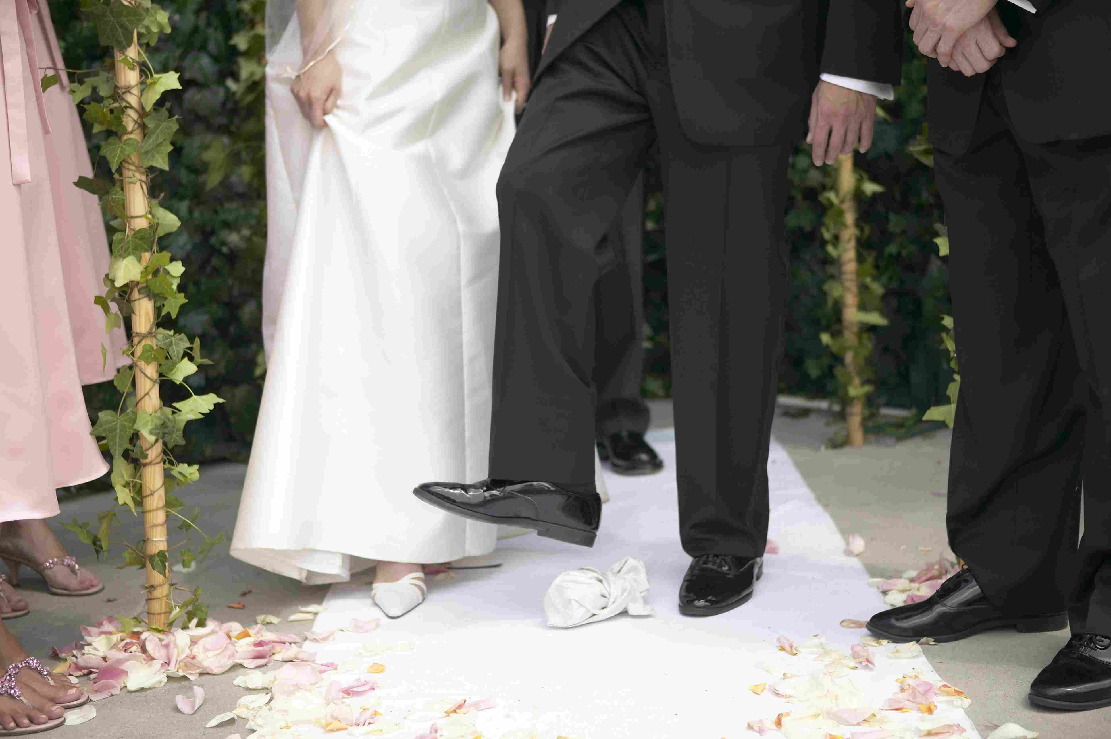 Groom stepping on glass during Jewish wedding ceremony