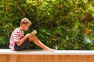 Full Length Of Boy Reading Book While Sitting On Building Terrace