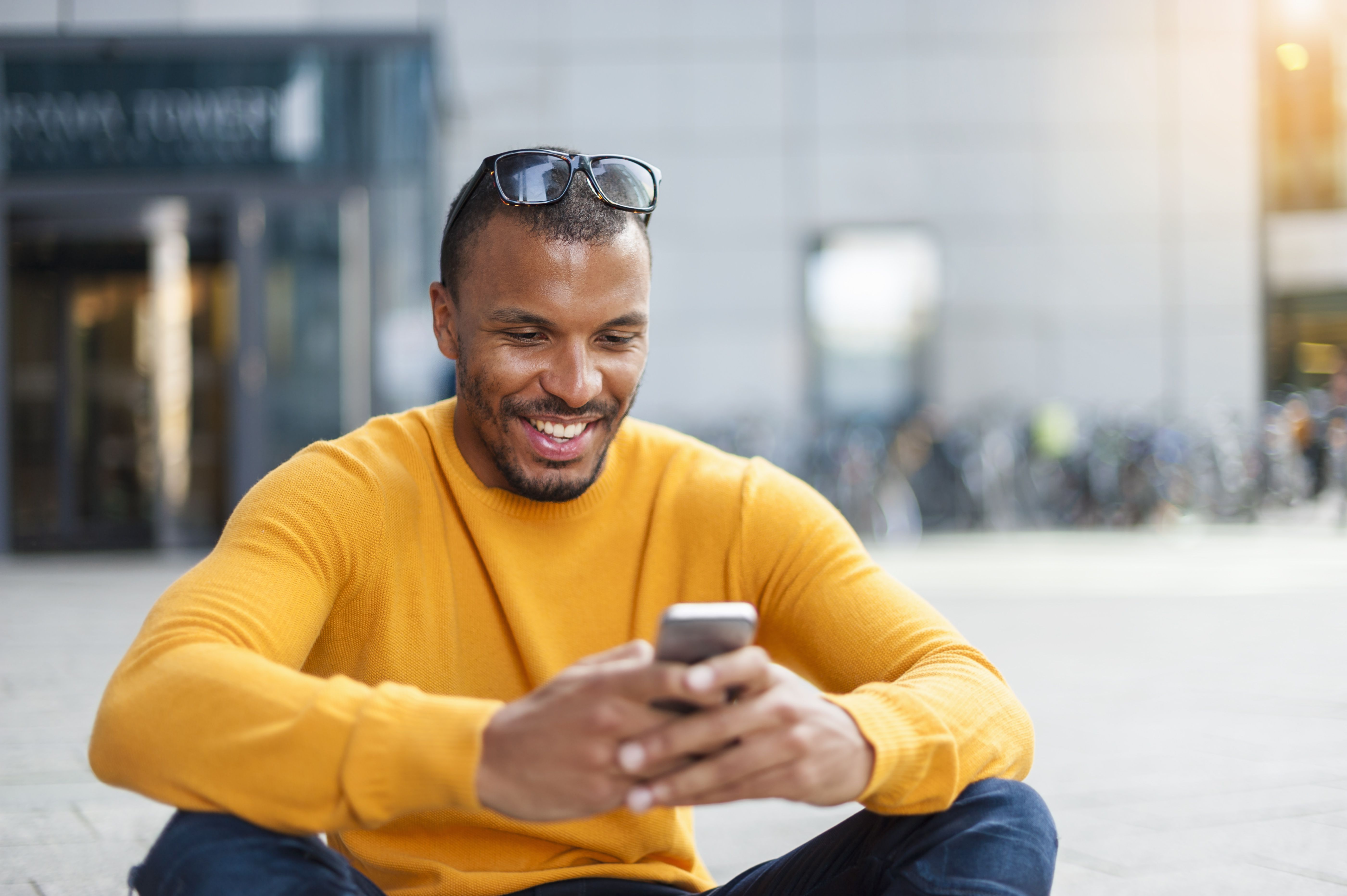 man wearing yellow pullover looking at cell phone