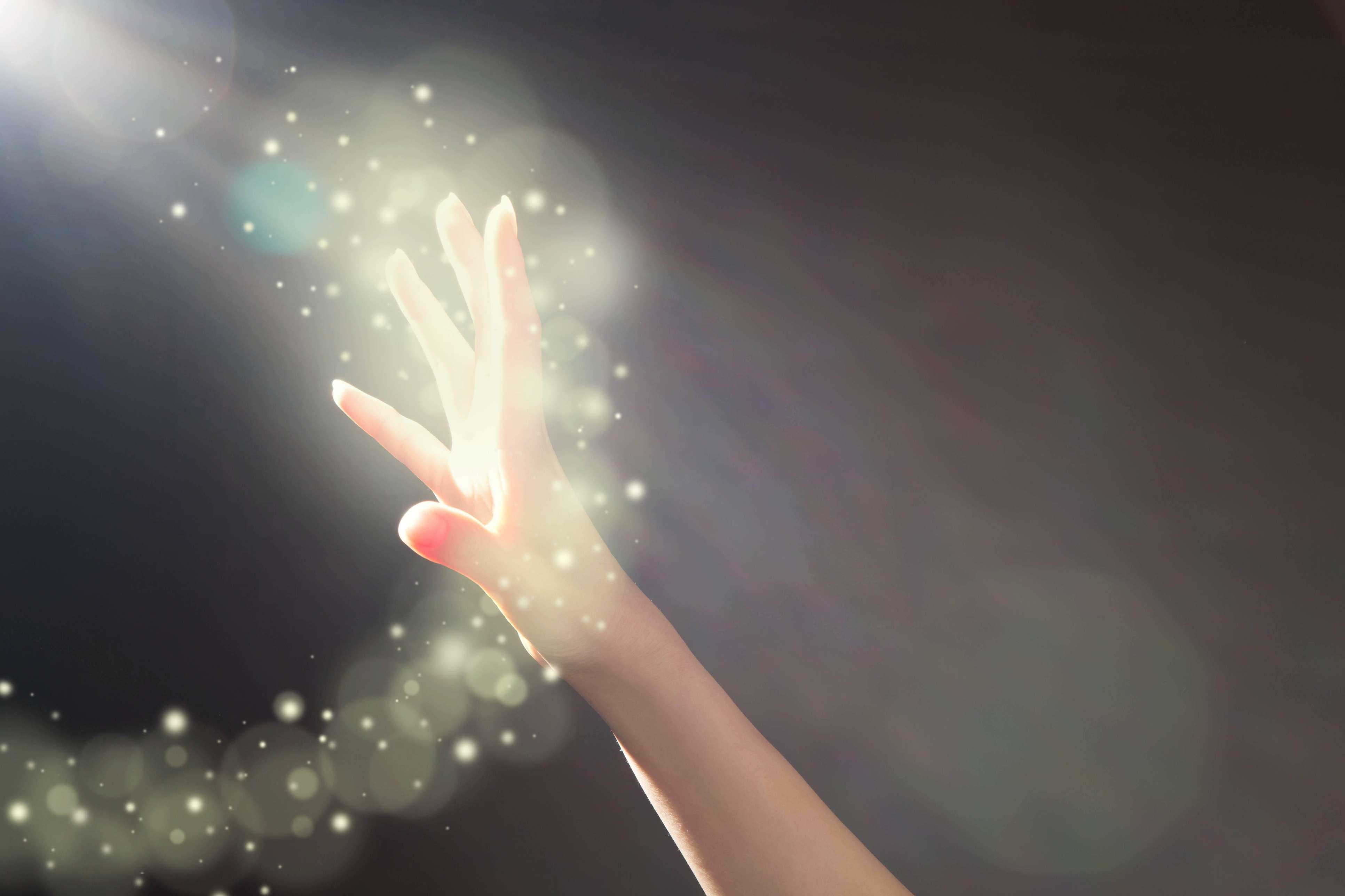 Hand reaching toward glowing light