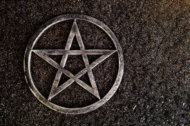 Gray metal pentagram on slate background with water drops