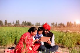 Cheerful Indian family sitting in the green wheat field during winter season & using I pad or Digital tablet. They all are wearing traditional Indian Dress while Using ipad in the field.