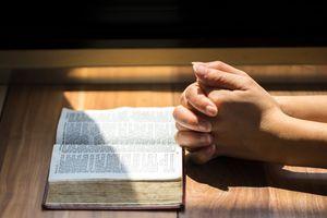 Praying hands next to a Bible