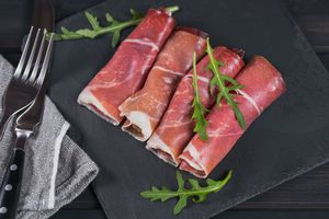 Black stone platter with slices of cured ham or Spanish jamon serrano or Italian prosciutto crudo